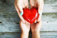 Mains de femme donnant un coeur rouge brillant à sa fille, partageant le concept d'amour images libres de droits