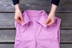 Mains de femme et collier rose de chemise Images libres de droits