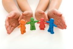 Mains de femme et d'enfant protégeant des gens de pâte à modeler photos stock