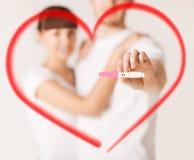 Mains de femme et d'homme avec l'essai de grossesse Photos libres de droits