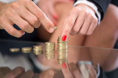 Mains de femme et d'homme construisant la colonne d'argent sur le bureau en verre Image stock