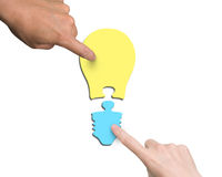 Mains de femme et d'homme deux assemblant un puzzle de forme d'ampoule Photographie stock