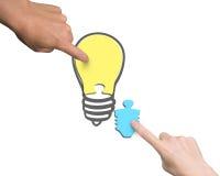 Mains de femme et d'homme deux assemblant un puzzle de forme d'ampoule Photos stock