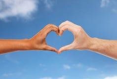 Mains de femme et d'homme faisant le symbole de coeur Images libres de droits