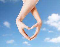 Mains de femme et d'homme faisant le symbole de coeur Photo stock