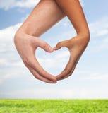 Mains de femme et d'homme montrant la forme de coeur Photographie stock libre de droits