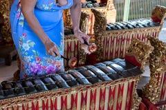 Mains de femme et instrument de musique traditionnel de Balinese gamelan ville courante de coucher du soleil de forme de bel Indo photographie stock libre de droits