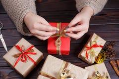 Mains de femme faisant l'arc au boîte-cadeau de Noël, décoré du gol Image libre de droits