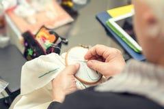 Mains de femme faisant la broderie à jour Photos stock