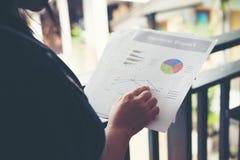 Mains de femme financière se dirigeant sur des notes de diagramme de finances tandis que W image stock