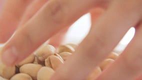 Mains de femme jouant avec la pistache banque de vidéos