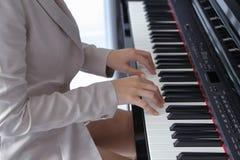 Mains de femme jouant le piano Photographie stock