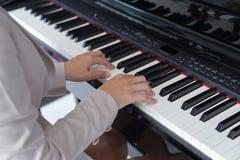 Mains de femme jouant le piano Photos stock