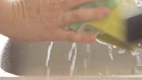 Mains de femme lavant des plats banque de vidéos