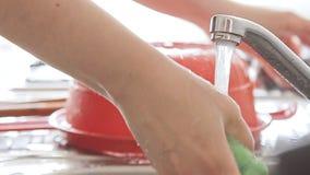 Mains de femme lavant la vaisselle de cuisine sous le courant de l'eau clips vidéos