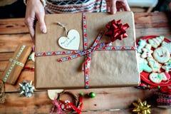 Mains de femme livrant un cadeau de Noël Image libre de droits