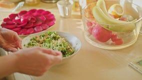 Mains de femme mélangeant la salade à la cuillère images libres de droits