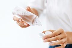 Mains de femme mettant le liquide de la bouteille dans la boîte de lentille Photo libre de droits