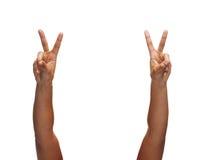 Mains de femme montrant le v-signe Photo stock