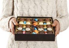 Mains de femme offrant des chocolats dans la boîte Photos libres de droits