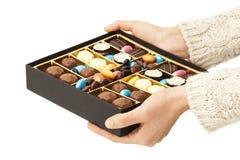Mains de femme offrant des chocolats dans la boîte Photographie stock libre de droits