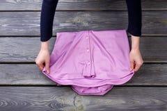 Mains de femme pliant des vêtements Photographie stock libre de droits