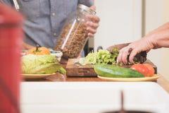 Mains de femme préparant des légumes dans la cuisine Photo stock