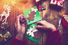 Mains de femme supérieure faisant le ` fait main s de nouvelle année ou le gi de Noël Photographie stock