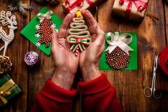 Mains de femme supérieure faisant le ` fait main s de nouvelle année ou le gi de Noël Photographie stock libre de droits