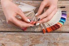 Mains de femme tenant des échantillons de clou d'été Photographie stock