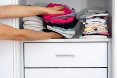 Mains de femme tenant l'habillement de toile coloré de textiles de pile photo stock