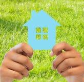Mains de femme tenant la maison bleue Image libre de droits