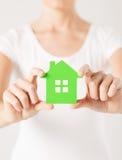 Mains de femme tenant la maison verte Images stock