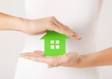 Mains de femme tenant la maison verte Image libre de droits