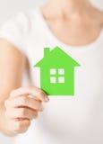 Mains de femme tenant la maison verte Photos stock