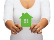 Mains de femme tenant la maison verte Photo stock