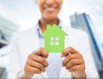 Mains de femme tenant la maison verte Image stock