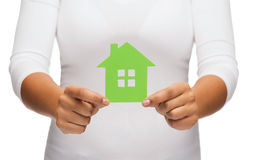 Mains de femme tenant la maison verte Photographie stock libre de droits