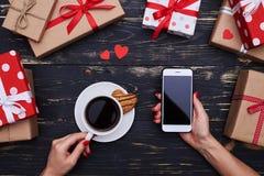 Mains de femme tenant la tasse de café dans un main et téléphone i Image stock