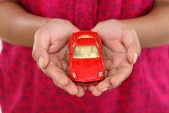 Mains de femme tenant la voiture rouge de jouet image libre de droits