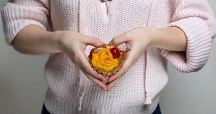 Mains de femme tenant le petit gâteau délicieux avec des baies et orange et faisant la forme de coeur photo stock