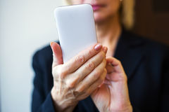 Mains de femme tenant le téléphone portable blanc closeup Photos stock