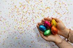 Mains de femme tenant les oeufs de p?ques color?s de chocolat avec le fond blanc et les confettis brouill?s color?s images libres de droits