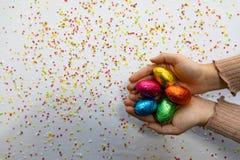Mains de femme tenant les oeufs de p?ques color?s de chocolat avec le fond blanc et les confettis brouill?s color?s photographie stock libre de droits