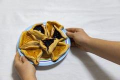Mains de femme tenant un plat color? avec des biscuits de confiture de myrtille et d'abricot de Hamantash Purim sur la nappe blan photo libre de droits