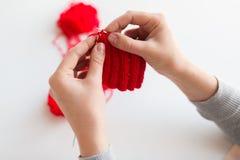 Mains de femme tricotant avec les aiguilles et le fil Image stock