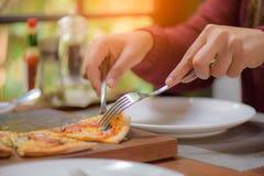 Mains de femme utilisant la cuillère et la fourchette prenant des tranches de pizza Images stock