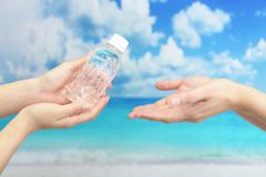 Mains de femmes avec une bouteille de l'eau Photographie stock libre de droits