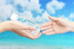 Mains de femmes avec une bouteille de l'eau Images libres de droits