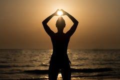 Mains de femmes formant un coeur avec la silhouette de coucher du soleil Image libre de droits